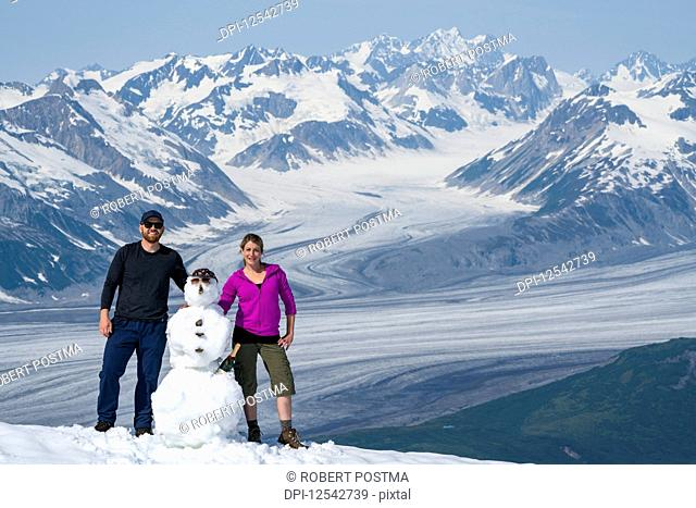 A couple enjoy the sights and scenery of Kluane National Park and Reserve on a bright sunny day after building a snowman; Haines Junction, Yukon, Canada