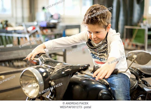 Boy pretending to drive vintage moped
