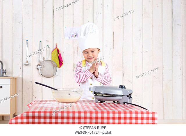 Little girl preparing waffles, wearing chef's hat