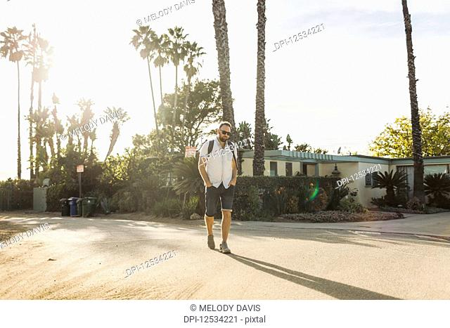 Man walks with a backpack on a residential street in a tropical climate; Long Beach, California, United States of America