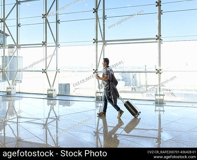 Man walking with suitcase at the departure hall of the airport