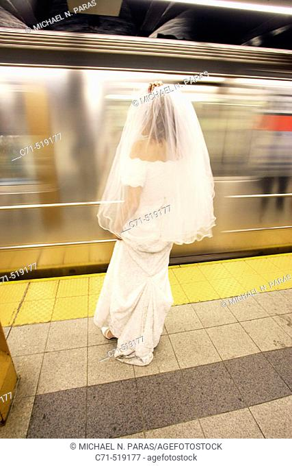 Bride in wedding dress on subway station platform with back to camera as train goes by in motion