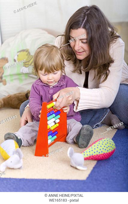girl one year old with mom and slide rule