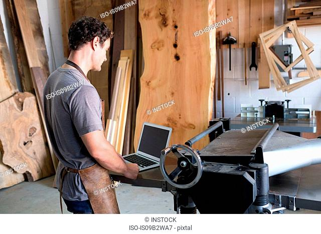Carpenter at his workshop, using laptop