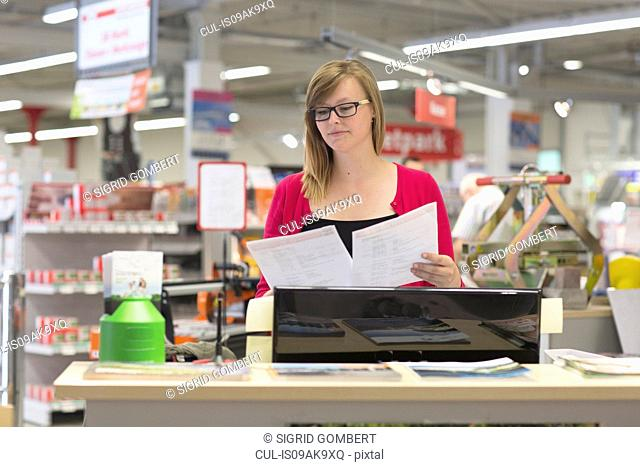 Female shop assistant checking orders in hardware store
