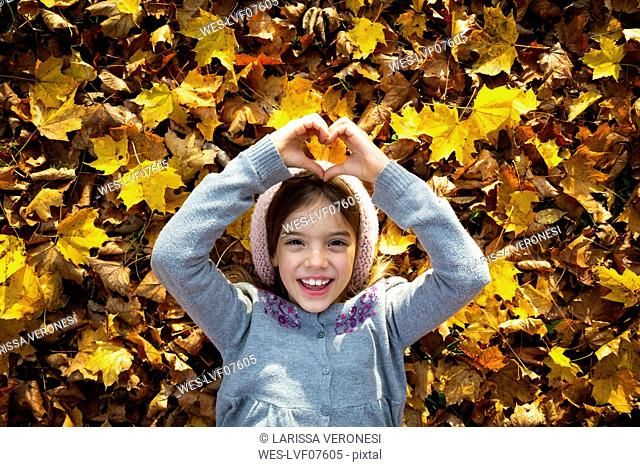 Portrait of happy little girl lying on autumn leaves shaping heart with her hands