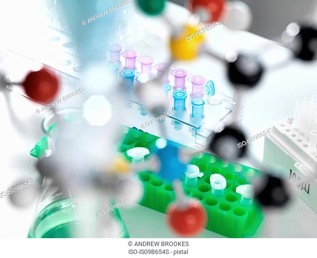 View through molecular model onto eppendorf tubes which are being used to test a sample in the laboratory