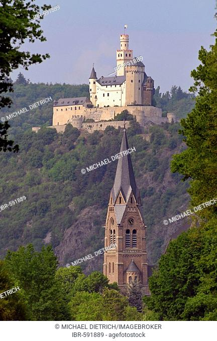Marksburg, a castle above the town of Braubach with the church St.Lambertus in Spay in the foreground, Middle Rhine, Rhineland-Palatinate, Germany