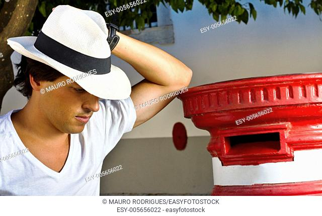 View of a handsome man with white shirt and hat on a urban city