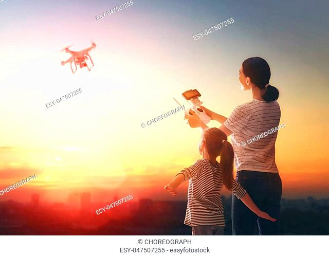 Little girl and her mother are operating the drone by remote control in the park. Kid and mom are playing with quadrocopter outdoors