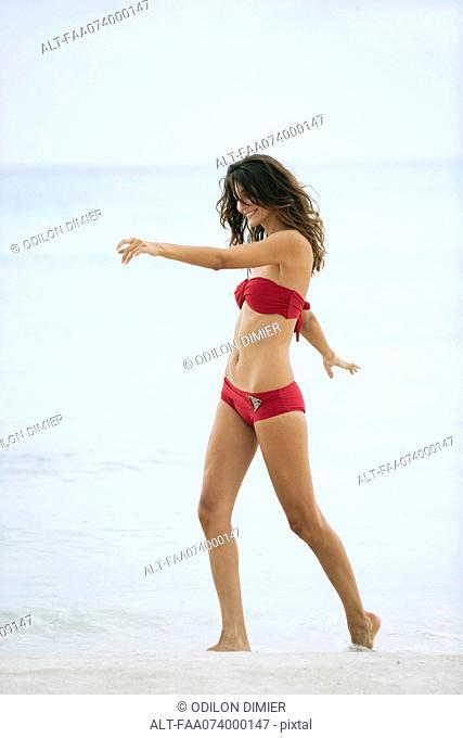 Woman in bikini walking in surf at the beach