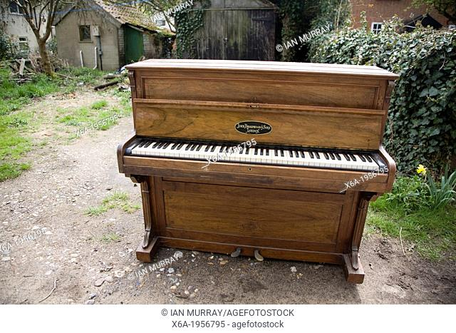 Abandoned piano standing outside in garden