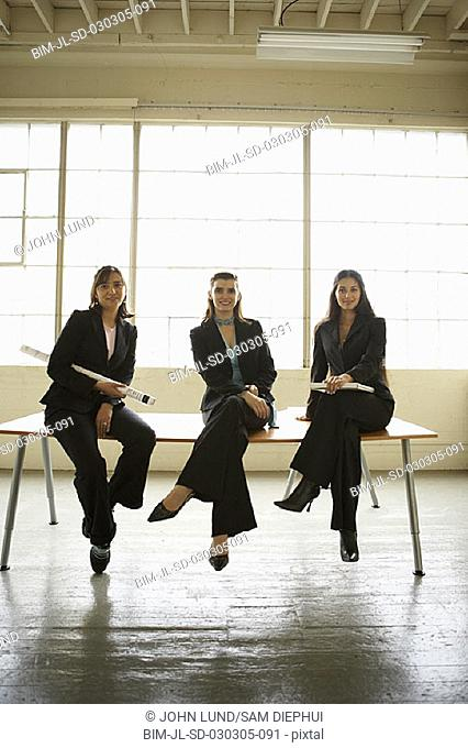 Portrait of businesswomen sitting on desk