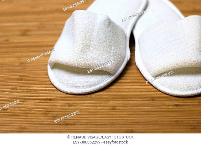 White slippers on a bamboo mat