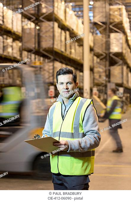 Worker writing on clipboard in warehouse