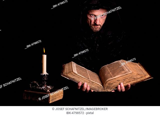 Man, with a black hooded coat, holding an old book in his hands, in front a burning candle, Germany