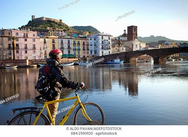 Temo river, cyclist overlooking the Old Bridge, Bosa, Sardinia, Italy