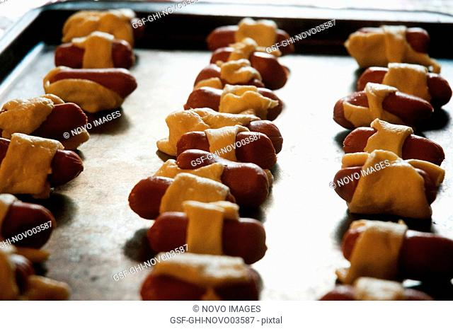 Pigs-in-a-Blanket Miniature Hot Dogs Wrapped in Pastry Dough on Baking Sheet