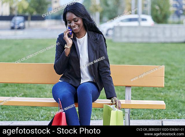 Young black woman talking on smartphone sitting in a park with r