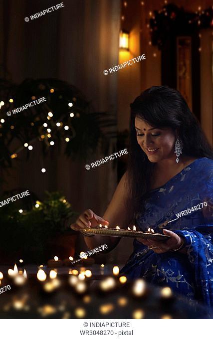 Woman arranging earthen lamps at diwali