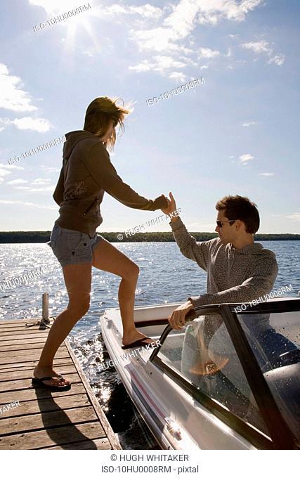 Couple climbing into speedboat