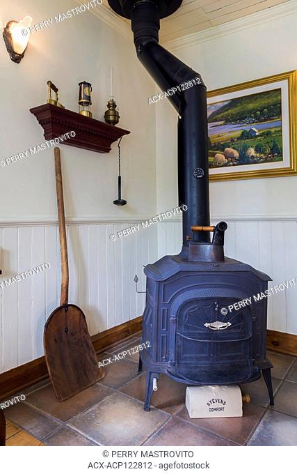 Black cast iron 1977 Vernon Casting wood burning stove in living room inside an old 1892 Canadiana cottage style home, Quebec, Canada