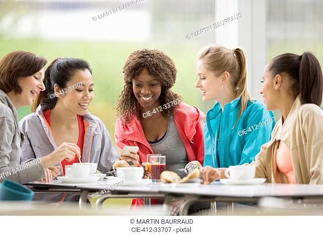 Smiling women friends drinking coffee and using cell phone post workout