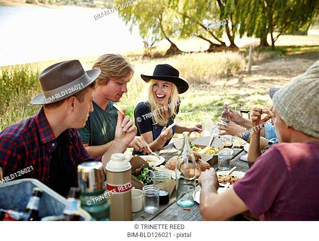 Friends eating at picnic table in park