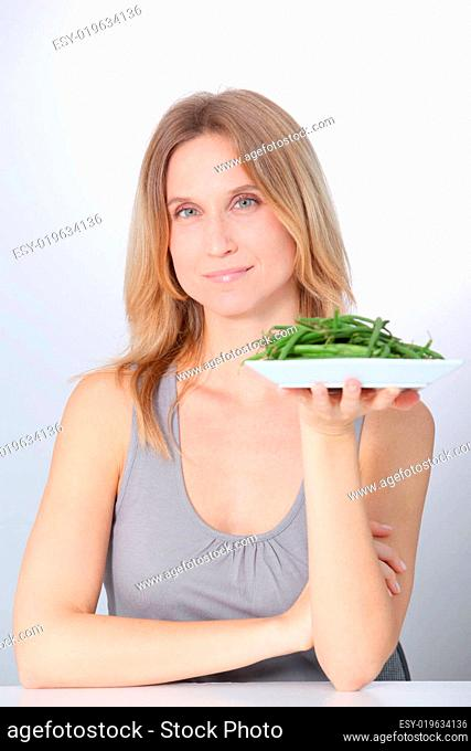 Woman in front of plate of green beans