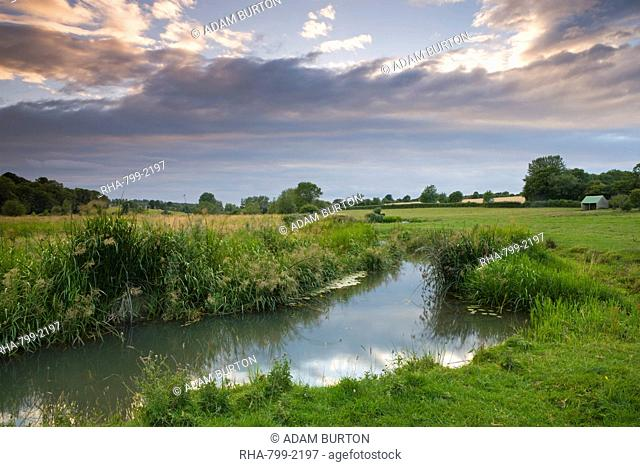 The River Windrush meanders through water meadows just outside the Cotswolds town of Burford, Oxfordshire, England, United Kingdom, Europe