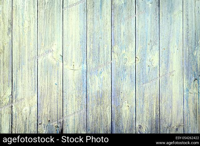 A fragment of a natural old wooden fence, painted with green paint . Presented close-up