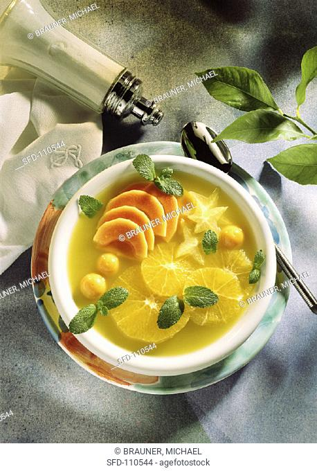 Lime soup with orange slices, kumquats, mango segments