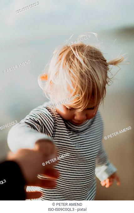 Adult holding toddler's hand outdoors