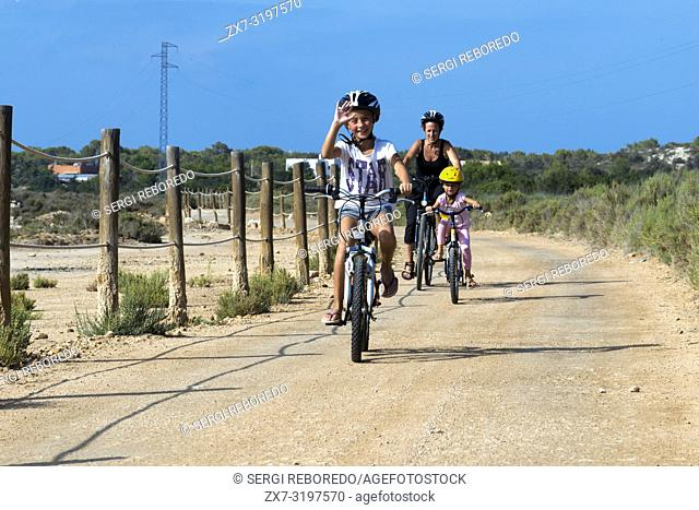 Mother and daughter are riding in a bike. Pudent Lake. Formentera. Balearic Islands, Spain, Europe. Bicycle route