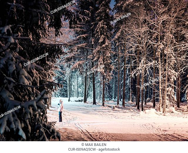 Mid adult woman standing on pathway in snowy forest, at night, Lahti, Finland