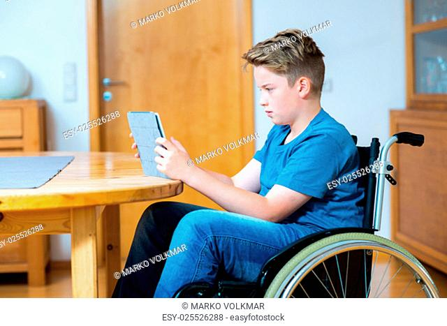 disabled boy in wheelchair chatting in the internet with tablet PC