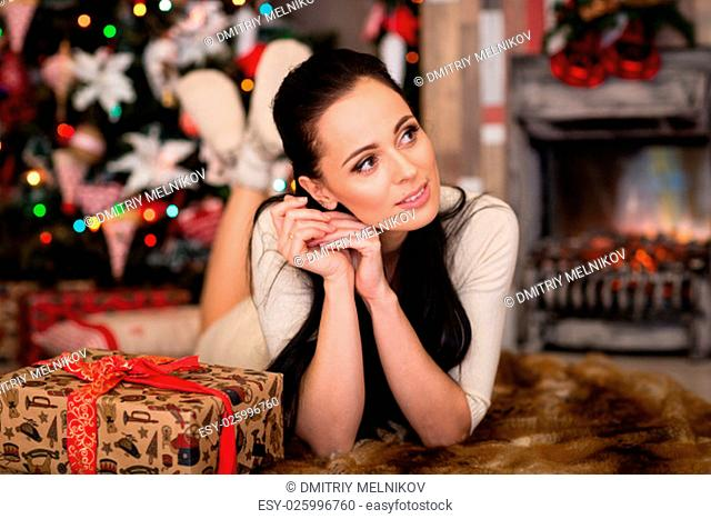 Young happy beautiful woman with gift box lies near Christmas tree in the room of the house. Merry Christmas and New Year
