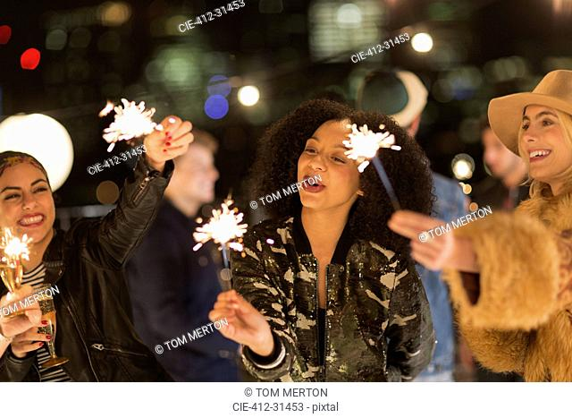 Young women waving sparklers at rooftop party