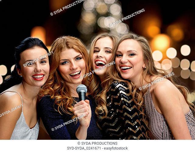 women with microphone singing karaoke at christmas