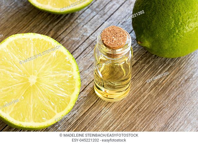 A bottle of lime essential oil with fresh limes in the background