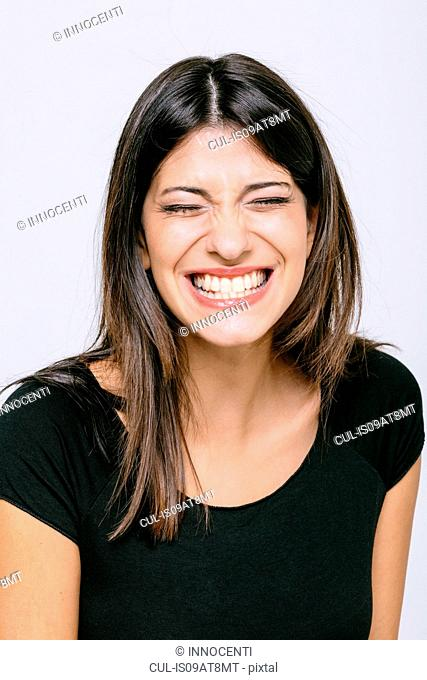 Head and shoulder portrait of young woman eyes closed toothy smile