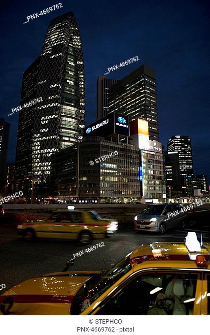 Yellow taxi and illuminated buildings at night time, Shinjuku, Tokyo, Japan