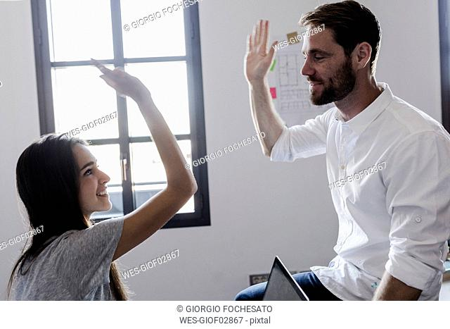 Happy couple at home high fiving