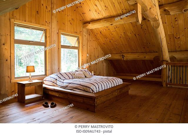 King size bed with wooden bed frame in the master bedroom, on mezzanine inside a handcrafted Eastern white pine cottage style log home, Quebec, Canada