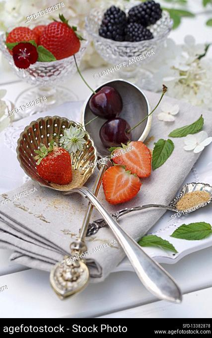 Still life with summer fruits in glass bowls and on silver spoons