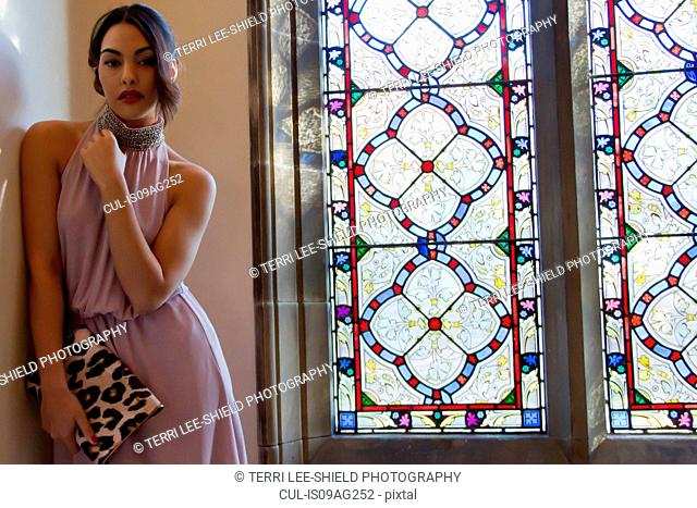 Portrait of feminine young woman next to stained glass window