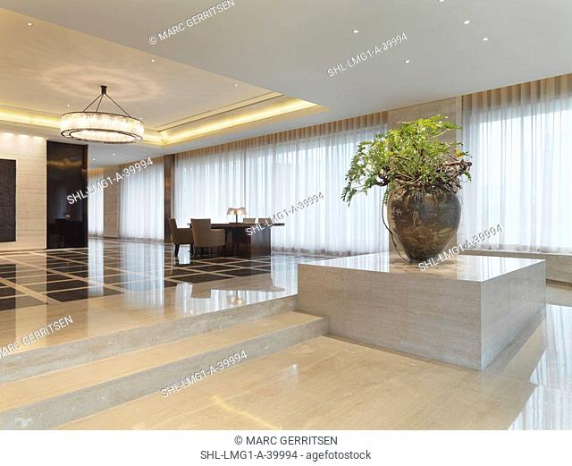 Modern lobby with large chadelier and marble floors