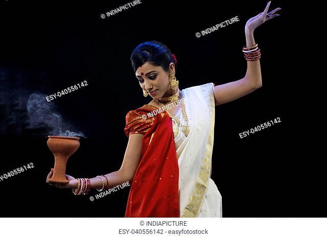 Bengali woman doing a Dhunuchi dance