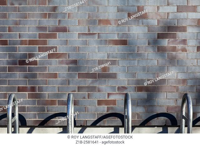 Abstract image of a brick wall with bike racks