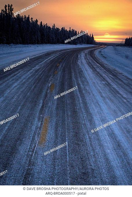Poor, icy snow-covered road conditions stand in contrast to a beautiful sunset outside Hay River, Northwest Territories in the Canadian north